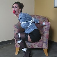 Ponytailed brunette slave in stockings Crissy Moran gets gagged and tied up on the armchair