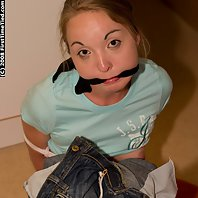 Marie is barefoot and dressed up in a top and jeans. She is tied and handcuffed. She is then made to