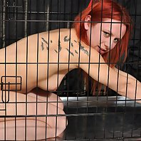 Naked slut tied up in a cage
