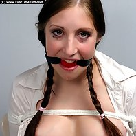 ballgagged and drools a lot.,Johanna is dressed up in her schoolgirl uniform and tied up on a chair.