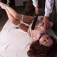 Lady stretched out upside down and flogged.