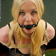 she got her legs tied up and she is big ballgagged.,high heels and stockings. She is tight harness t